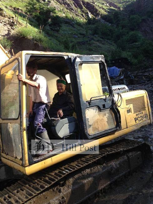 Chief minister Virbhadra Singh, riding a excavator to get to a nearby helipad in Sangla, Kinnaur