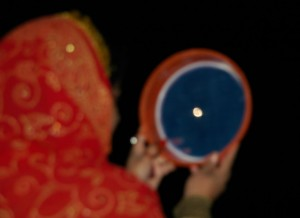 Woman pray during the Hindu festival of Karva Chauth  in the northern hill town of Shimla on October 7, 2009. Married Hindu women observe a one-day fast during the festival and offer prayers for the well-being of their husbands. The fast begins before sunrise and ends after they worship the moon in the evening.