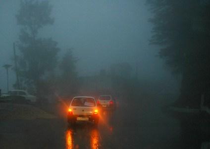 Vehicles make their way through foggy roads