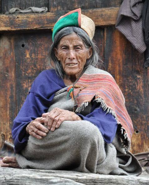 An elderly woman sitting outside her house, in traditional #Kinnauri outfit