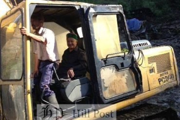 June File Photo of a stranded Virbhadra Singh, the chief minister riding a excavator to get to a nearby helipad in Sangla, Kinnaur