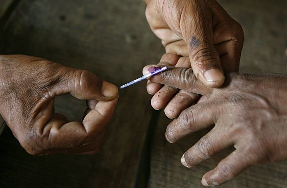 Polling officer applies ink on the finger on voters finger